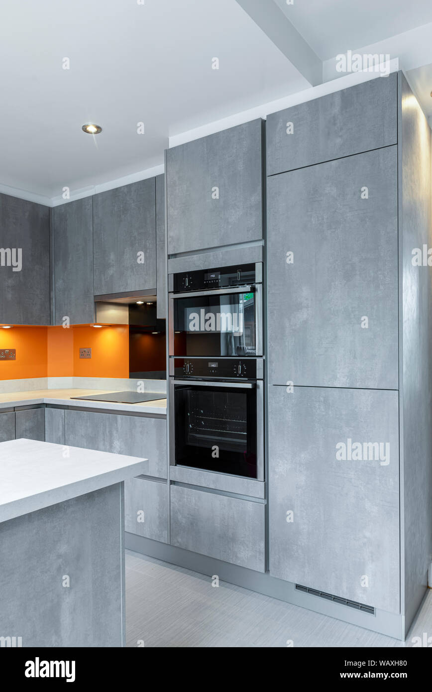 Modern Luxury Minimalist Domestic Kitchen Concrete Style Grey Cabinets And A Pop Of Orange On The Walls Stock Photo Alamy