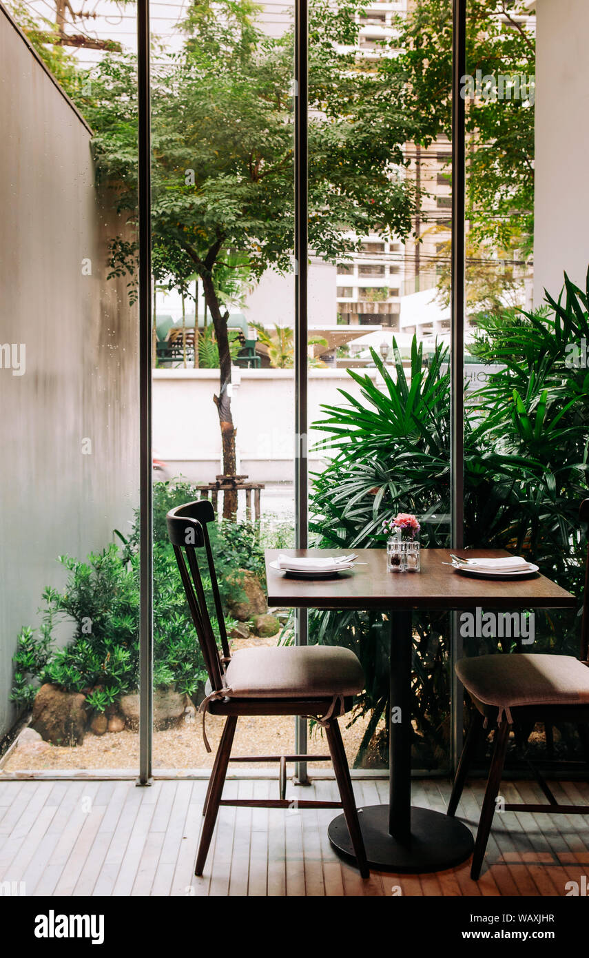 Oct 17 2013 Bangkok Thailand Contemporary Designed Wooden Dinner Table In Modern Restaurant With Tropical Garden View Through Glass Wall Stock Photo Alamy