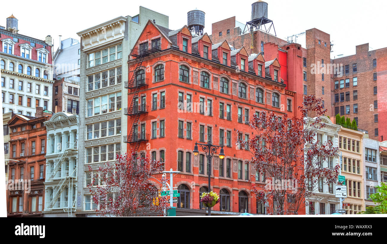 Colorful brick buildings, with windows and fire stairs. Water deposits on rooftops. NYC, USA Stock Photo