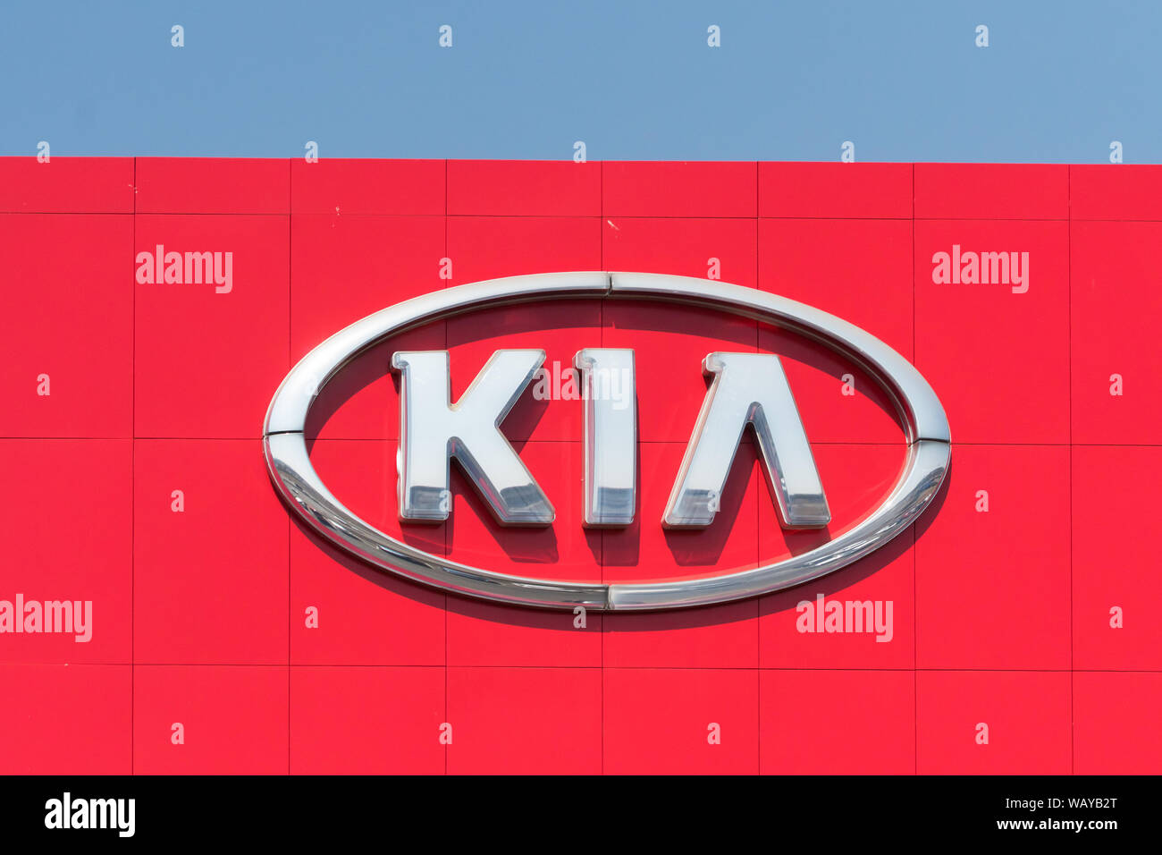 KIA silver sign or signage emblem logo against a bright red facade of a building in Johannesburg, Gauteng, South Africa Stock Photo