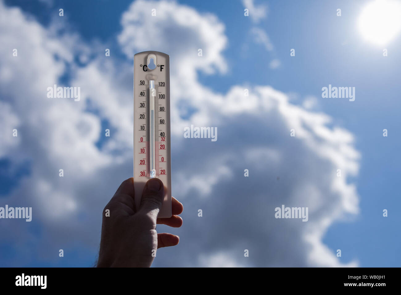 Man keep thermometer in hand at sky with clouds background. Weather concept Stock Photo