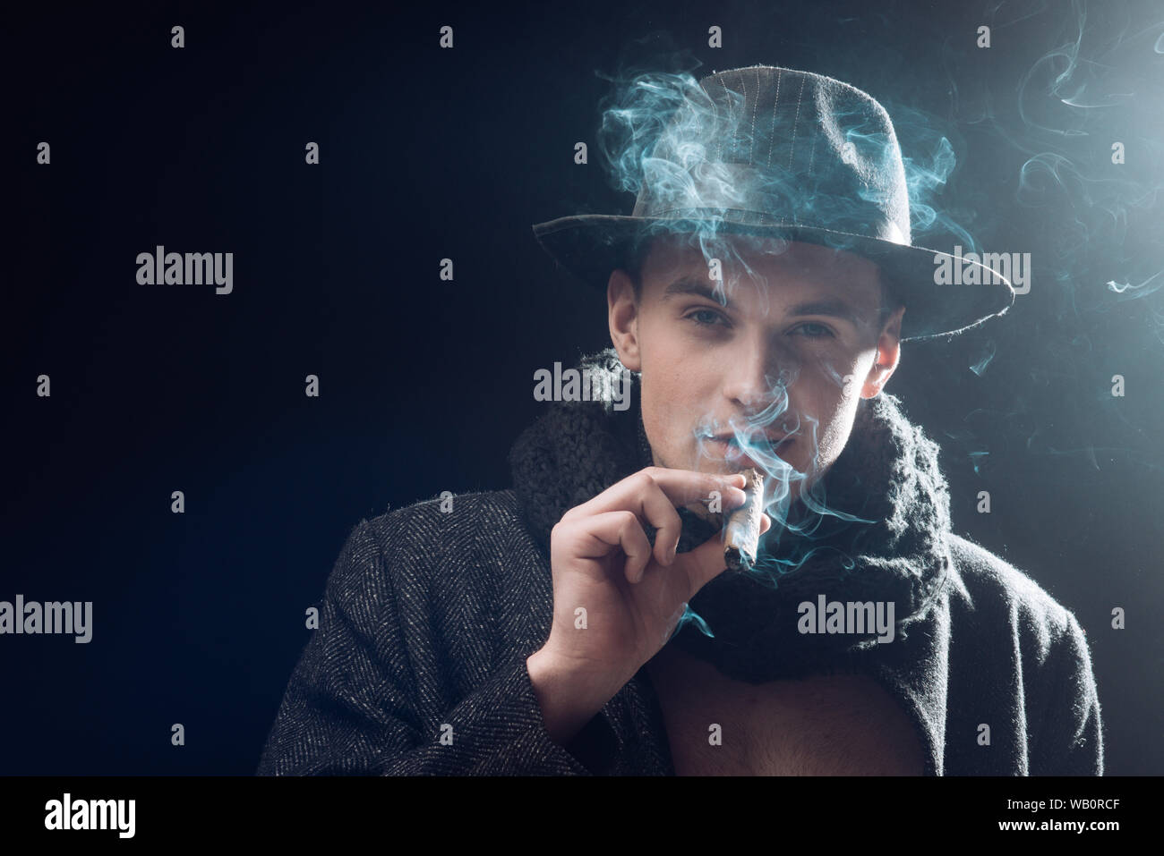 Man in coat, hat smoking cigar, dark background. Macho on mysterious face, detective, investigator, agent. Guy in old fashioned outfit looks mysteriou Stock Photo