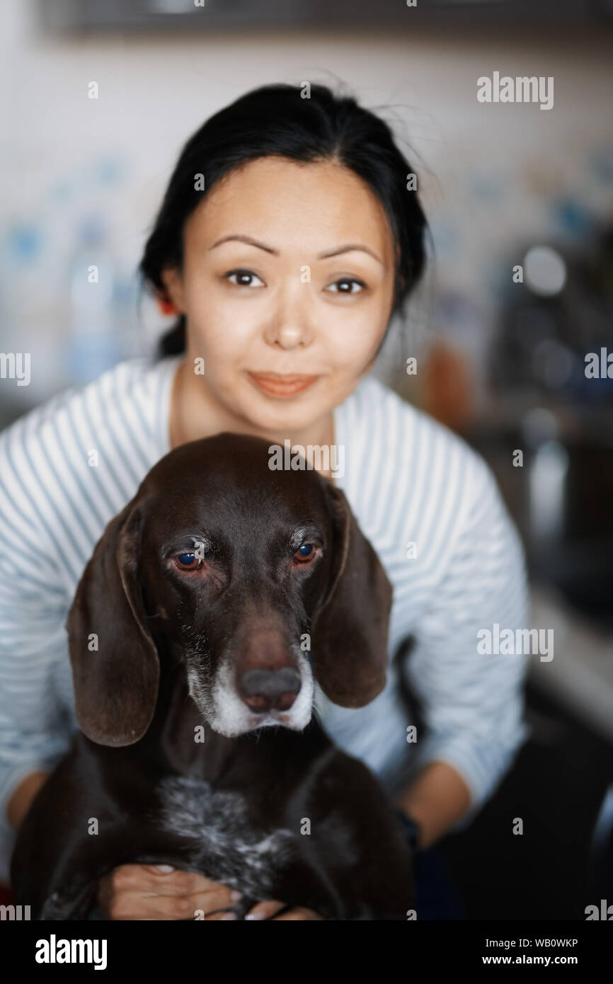 Woman at home hugging her dog Stock Photo