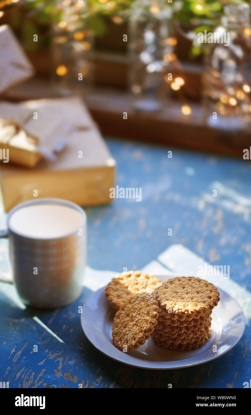Teacup and Christmas gluten free cookies on a table near the decorated window with gift boxes Stock Photo