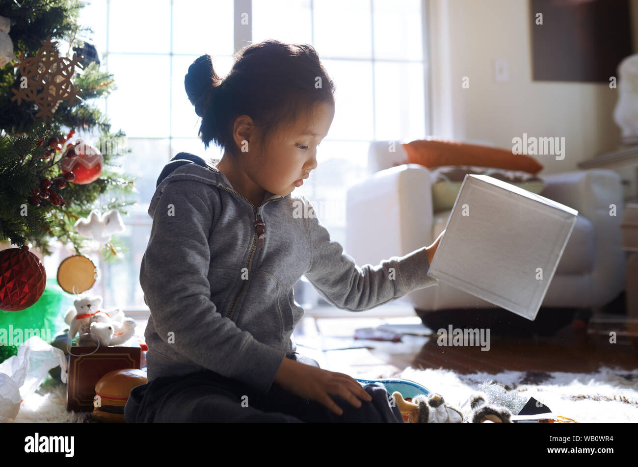 Little girl playing with gift and boxes at the Christmas tree Stock Photo