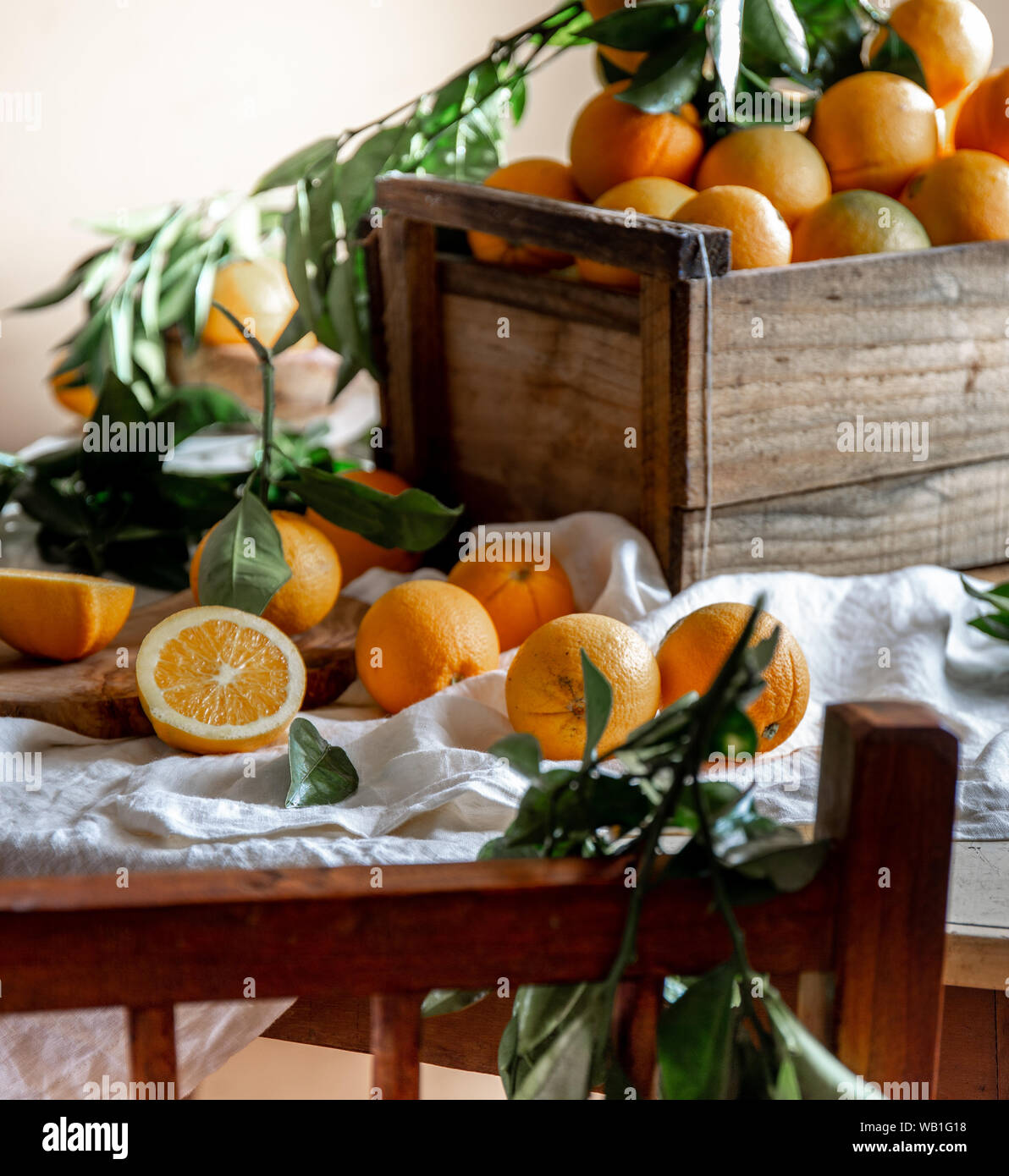Table with box of fresh orange with orange tree branch and fresh orange juice Stock Photo