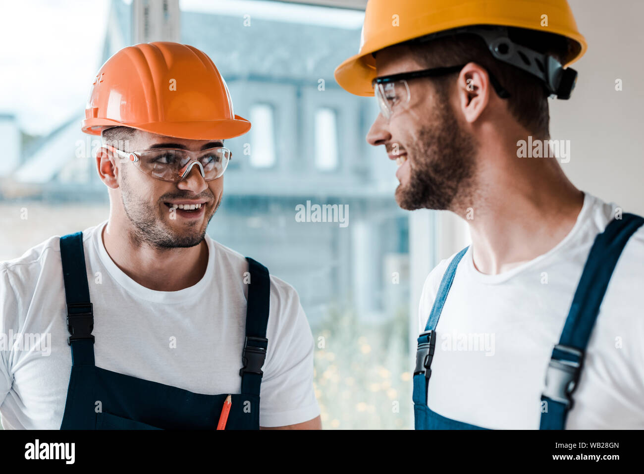 happy repairmen in helmets and goggles looking at each other Stock Photo