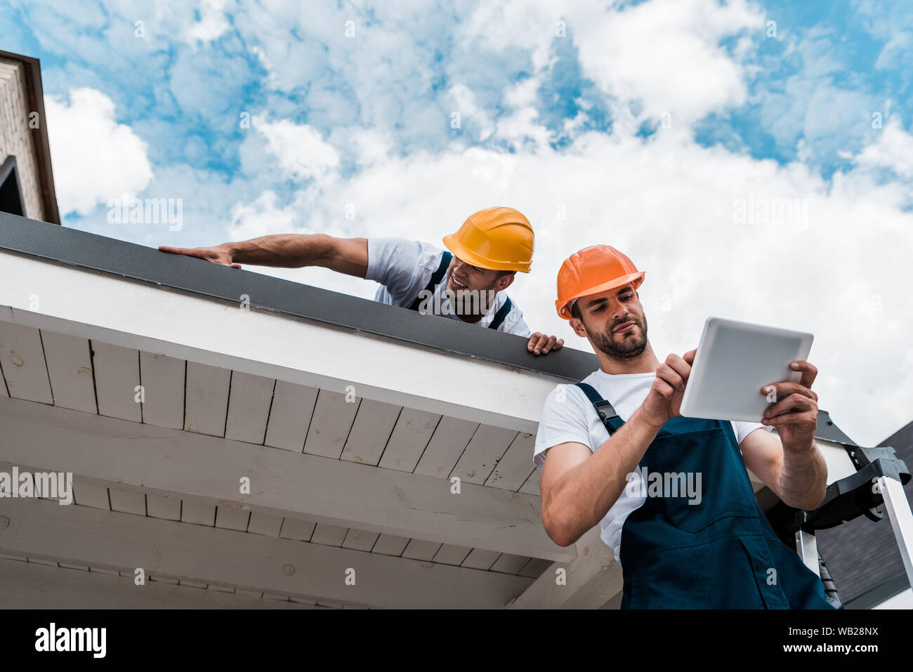 low angle view of handsome handyman using digital tablet near coworker on roof Stock Photo