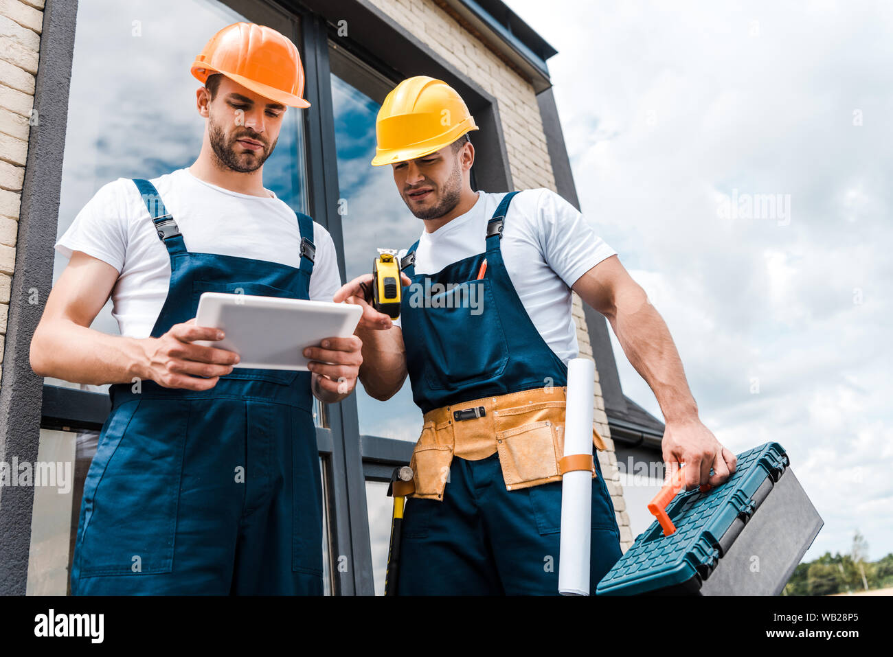 low angle view of handsome repairmen looking at digital tablet Stock Photo