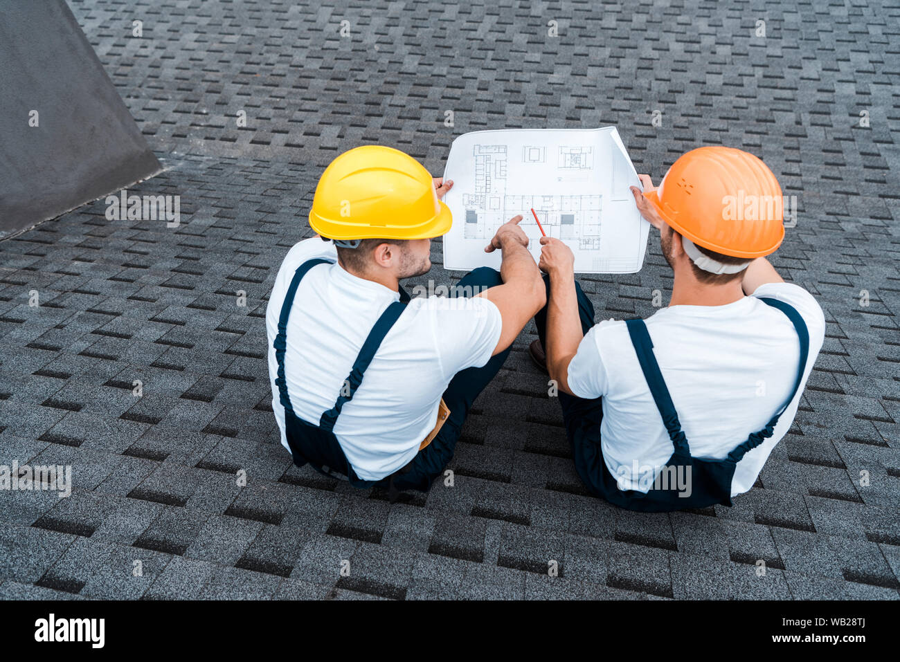 Overhead View Of Architects In Helmets Sitting On Roof With