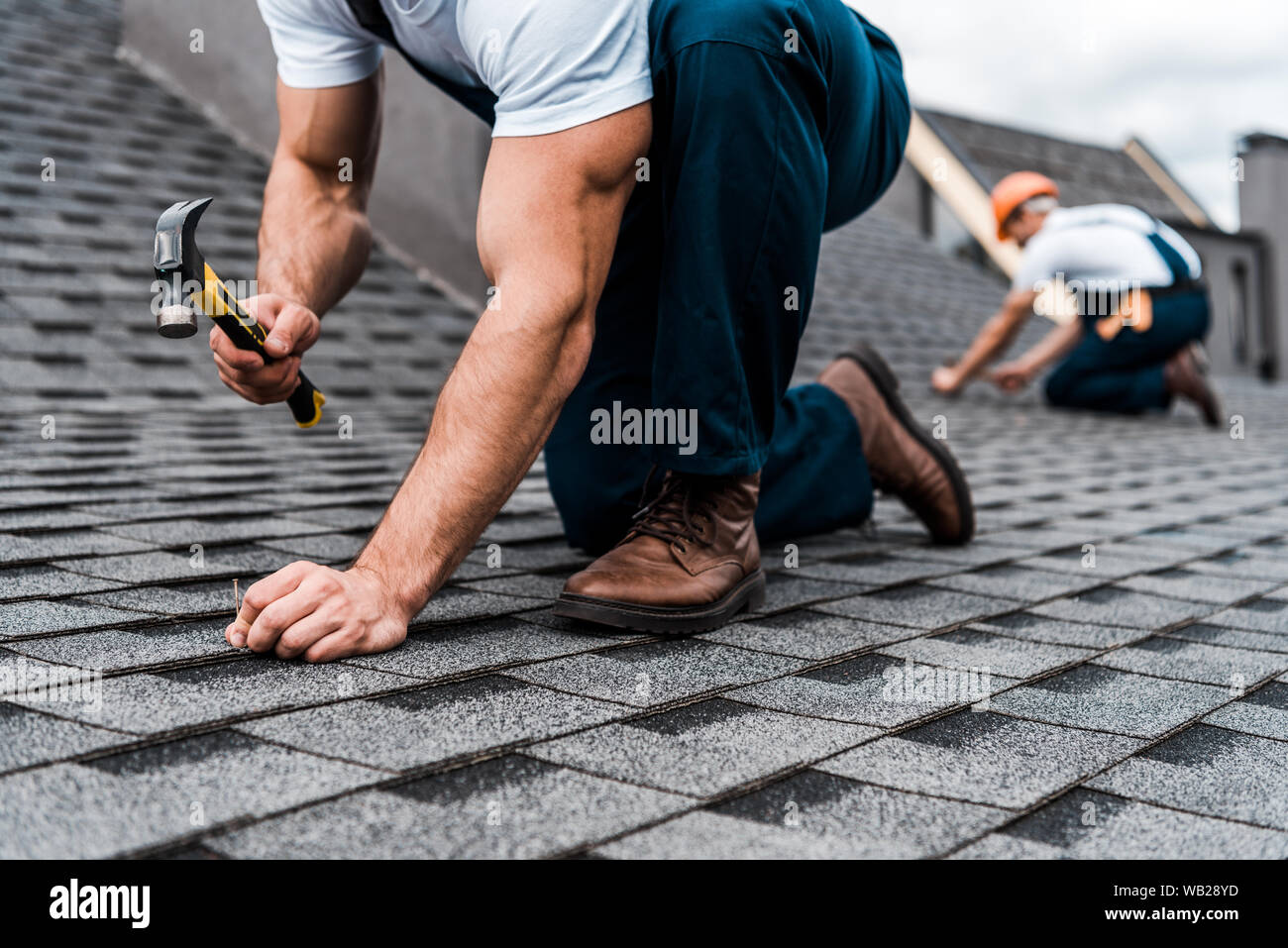 cropped view of repairmen in uniform working on rooftop Stock Photo
