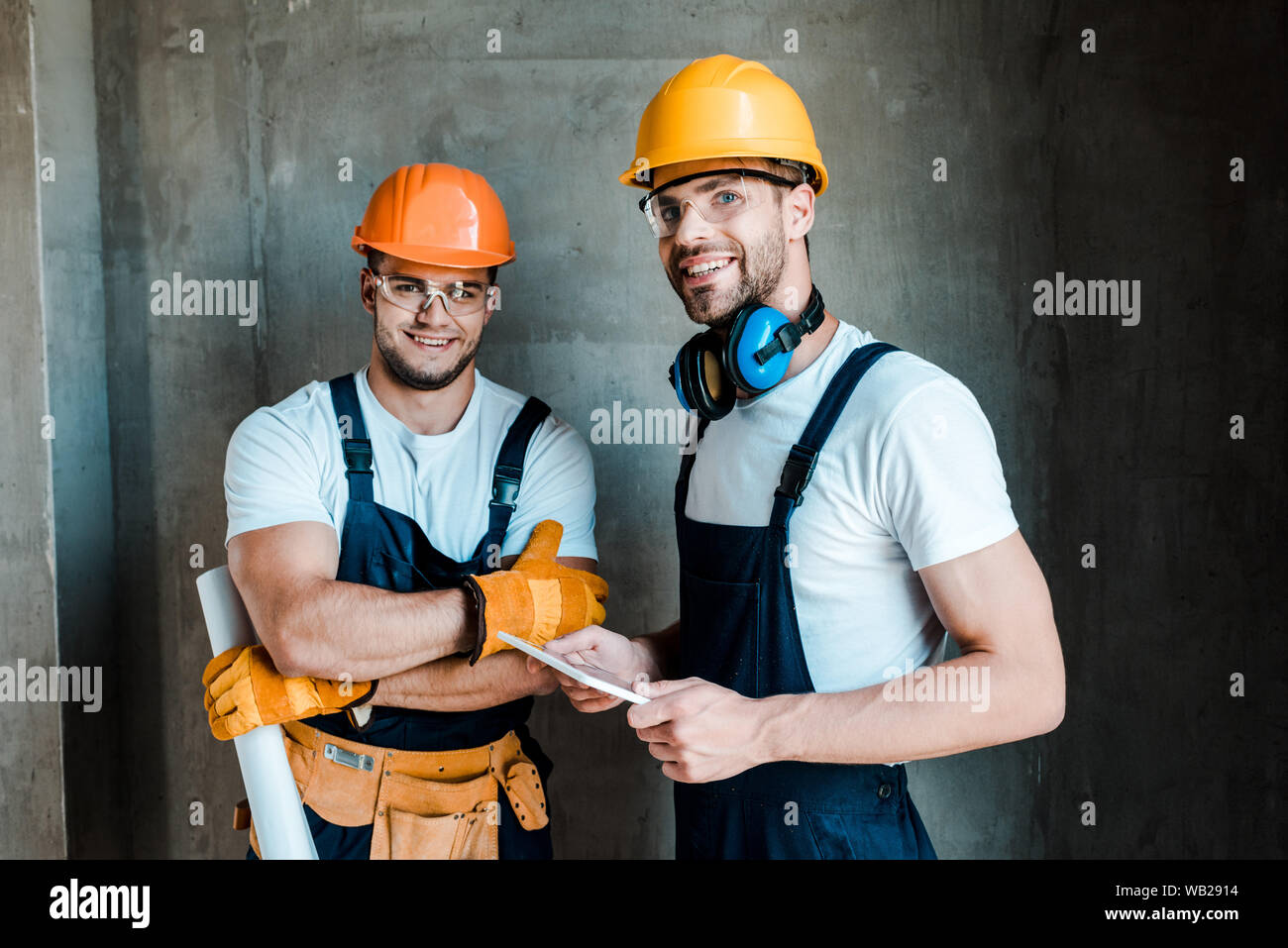 happy repairmen in goggles and helmets standing in house Stock Photo