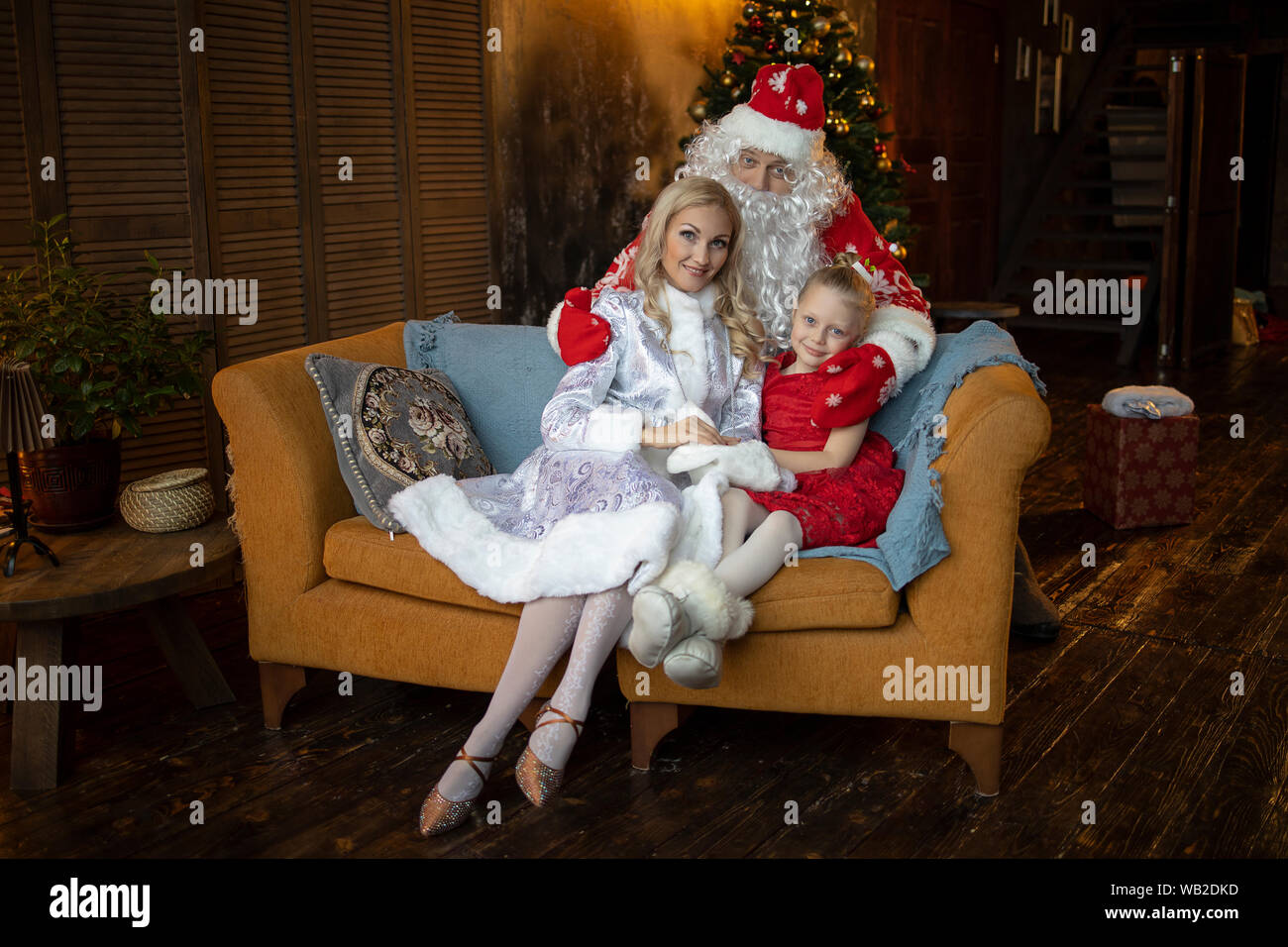 Santa Claus hugs his assistants Snow Maiden and daughter gnome Stock Photo