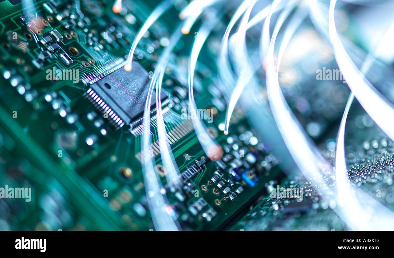 Digital communication, conceptual image. Fibre optics carrying data over electronic circuitry on a laptop computer. Stock Photo
