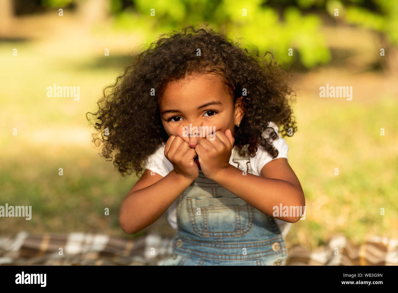 Little girl grimacing and touching cheeks in nature park Stock Photo