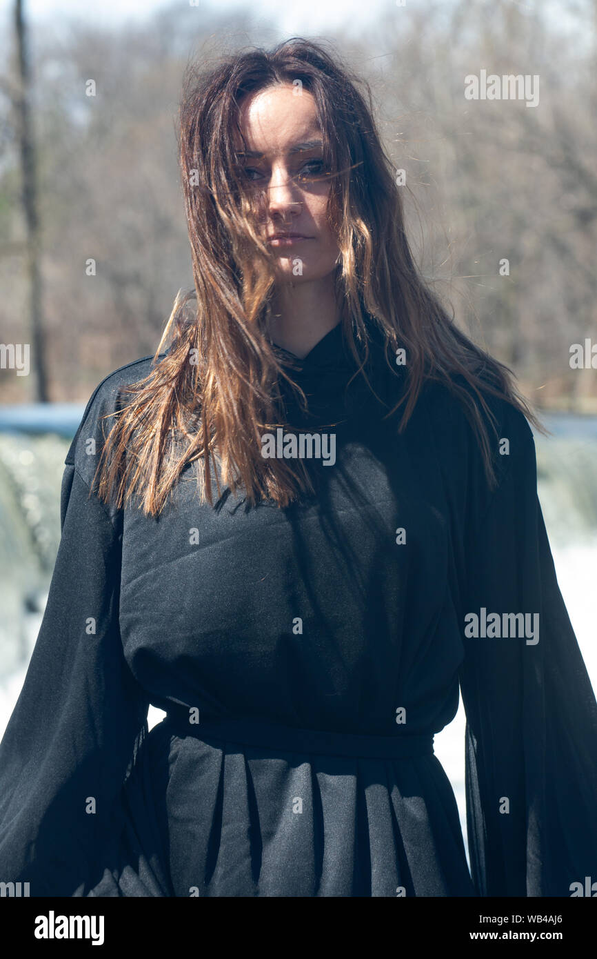 Young Tall Woman With Dark Long Hair In Black Robes In Front Of The Waterfall Witches Halloween Concept Witchcraft And Magic Stock Photo Alamy