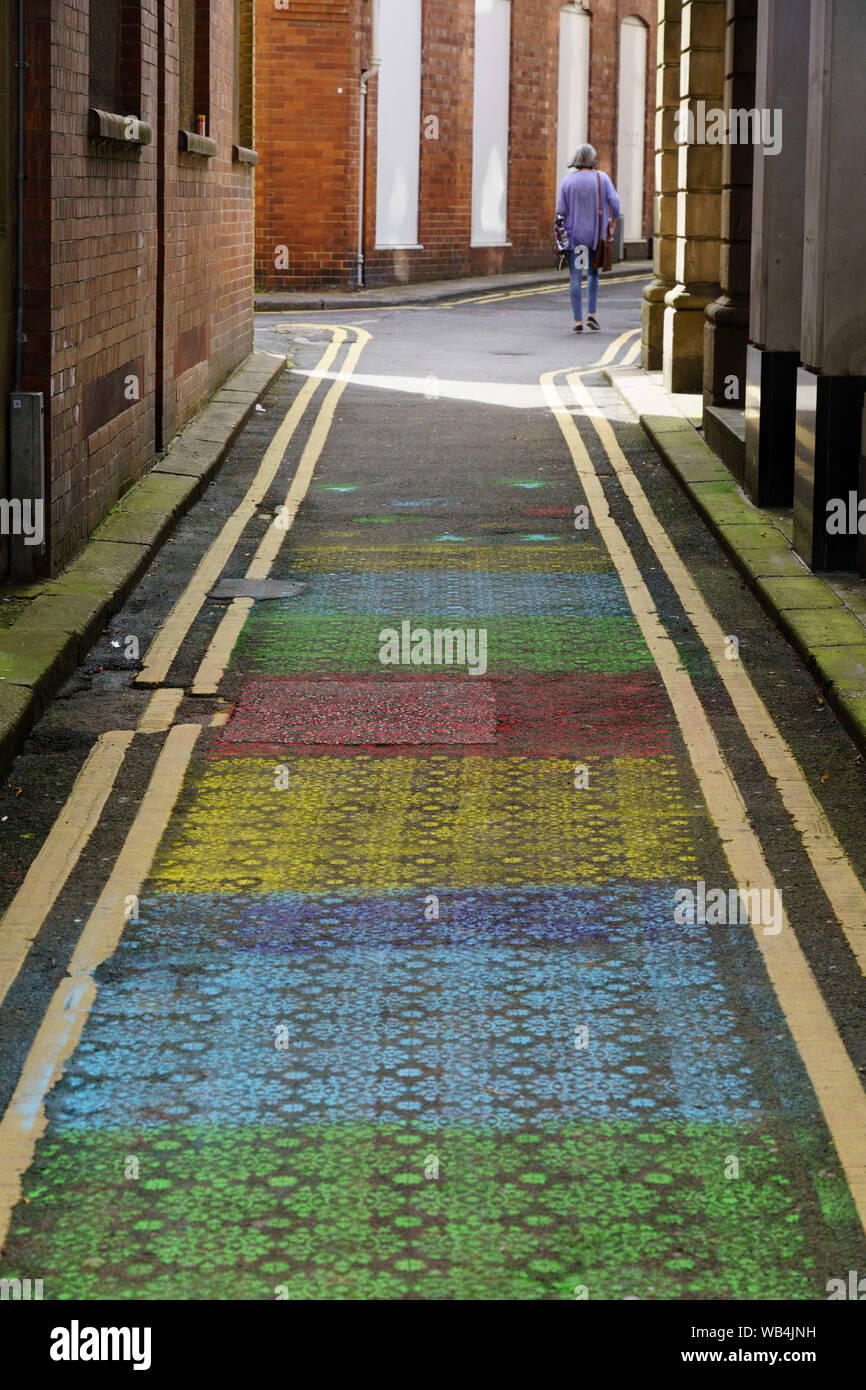 Woman walking along a narrow road decorated with colourful stencil patterns, Harrogate, North Yorkshire, England, UK. Stock Photo