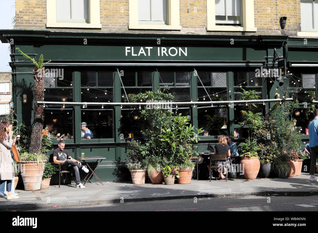 Flat iron pub and people tourists in summer on Commercial Street in Spitalfields East London E1 England UK    KATHY DEWITT Stock Photo