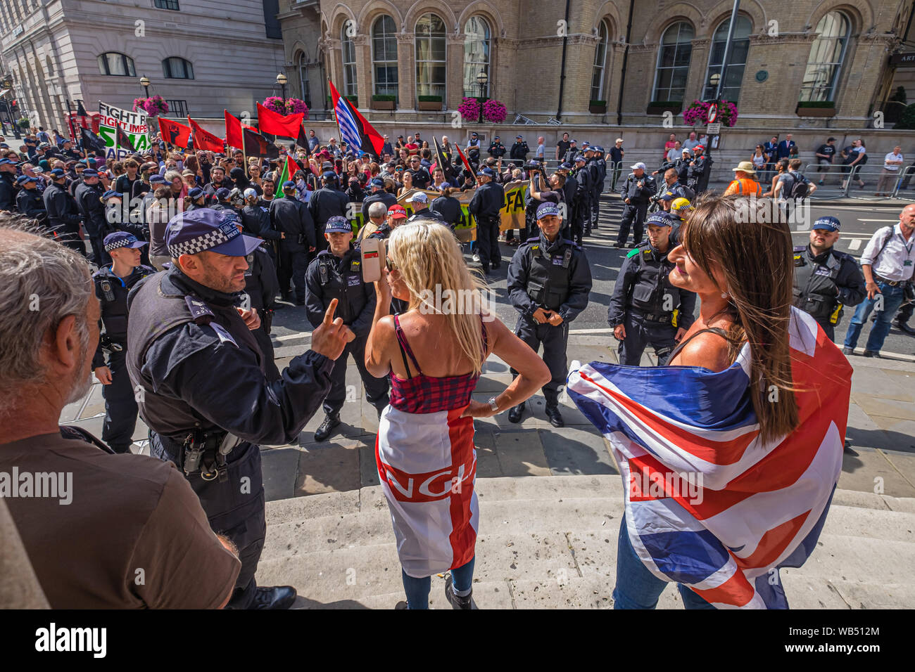 London, UK. 24th August 2019. A woman at the protest at the BBC by Tommy Robinson supporters is warned by the police for offensive language. The protesters claim he is in jail for journalism. He was sentenced to 9 months for 3 offences outside Leeds Crown Court which could have led to the collapse of a grooming gang trial, and has previous convictions for violence, financial and immigration frauds, drug possession and public order offences. Police kept the two groups apart. Robinson supporters were later joined by marchers from Trafalgar Square, and a larger group from Stand Up to Racism came Stock Photo