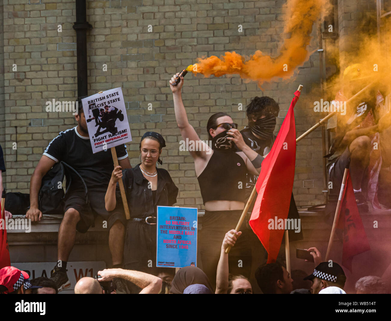London, UK. 24th August 2019. Anti-fascists hold placards and flares as they oppose a protest at the BBC by Tommy Robinson supporters who claim he is in jail for journalism. He was sentenced to 9 months for 3 offences outside Leeds Crown Court which could have led to the collapse of a grooming gang trial, and has previous convictions for violence, financial and immigration frauds, drug possession and public order offences. Police kept the two groups apart. Robinson supporters were later joined by marchers from Trafalgar Square, and a larger group from Stand Up to Racism came to join Antifa. Pe Stock Photo