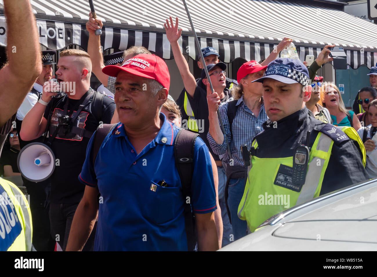 London, UK. 24th August 2019. Police escort marchers coming to join the protest at the BBC by Tommy Robinson supporters who claim he is in jail for journalism. He was sentenced to 9 months for 3 offences outside Leeds Crown Court which could have led to the collapse of a grooming gang trial, and has previous convictions for violence, financial and immigration frauds, drug possession and public order offences. Police kept the two groups apart. Robinson supporters were later joined by marchers from Trafalgar Square, and a larger group from Stand Up to Racism came to join Antifa. Peter Marshall/A Stock Photo