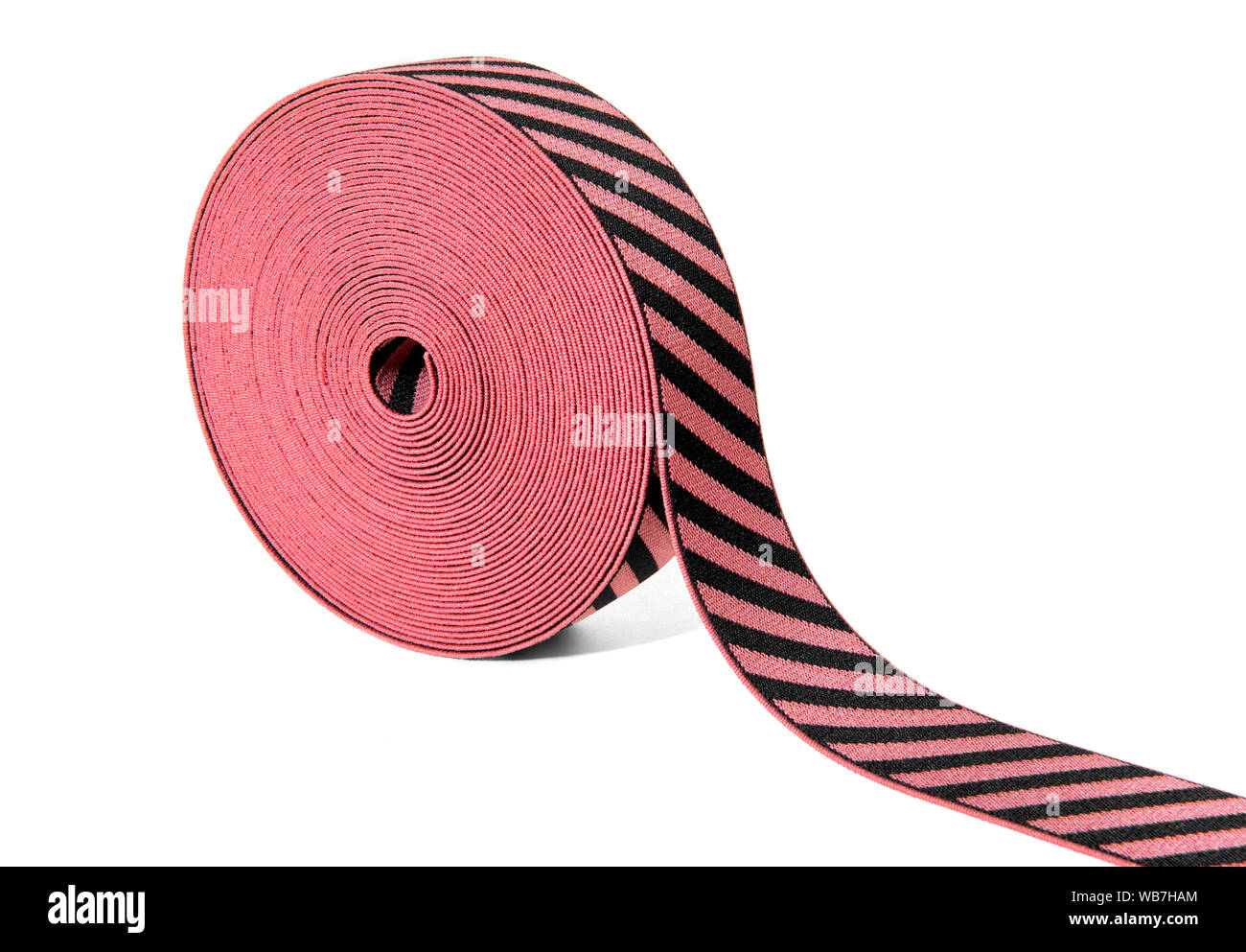 Roll of decorative elastic ribbon in red and black with alternating diagonal stripes displayed at an angle on white with copy space Stock Photo