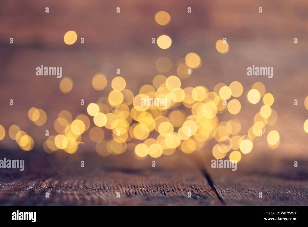 Gold rays of light with bubbles and glitters on wooden background Stock Photo