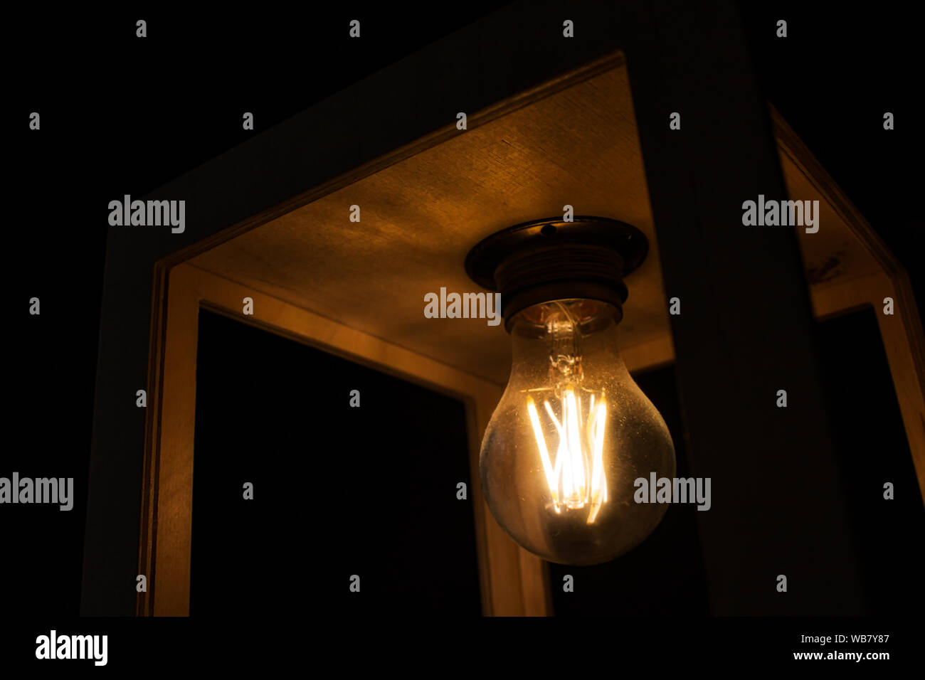 Close-up of warm yellow glowing light bulb encased in a wooden box against a black background Stock Photo