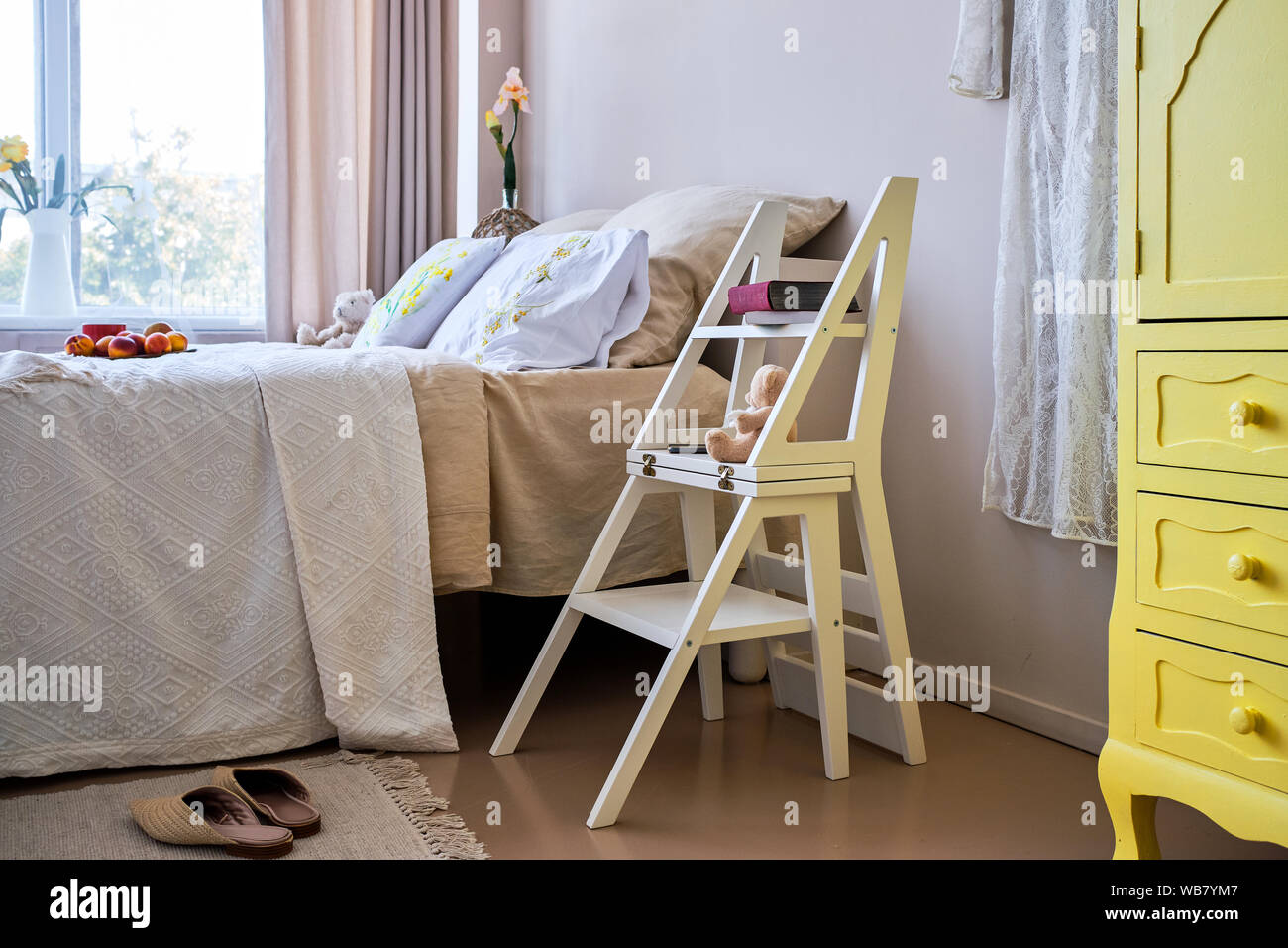 Use of folding stepladder chair in bedroom Stock Photo