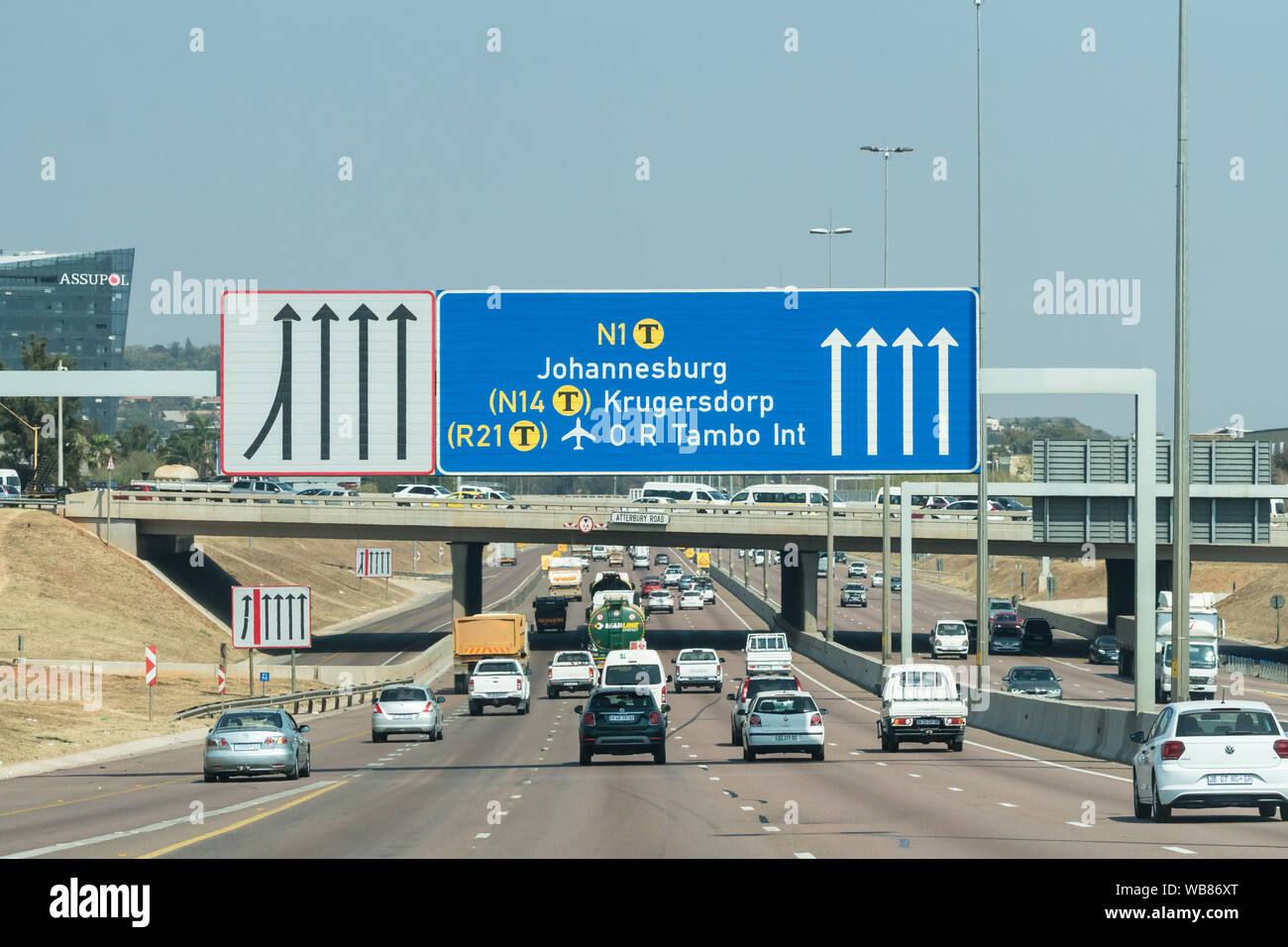 cars and vehicles speed along the N1 highway toll road with a blue sign board and directions to the city of Johannesburg,Gauteng, South Africa Stock Photo