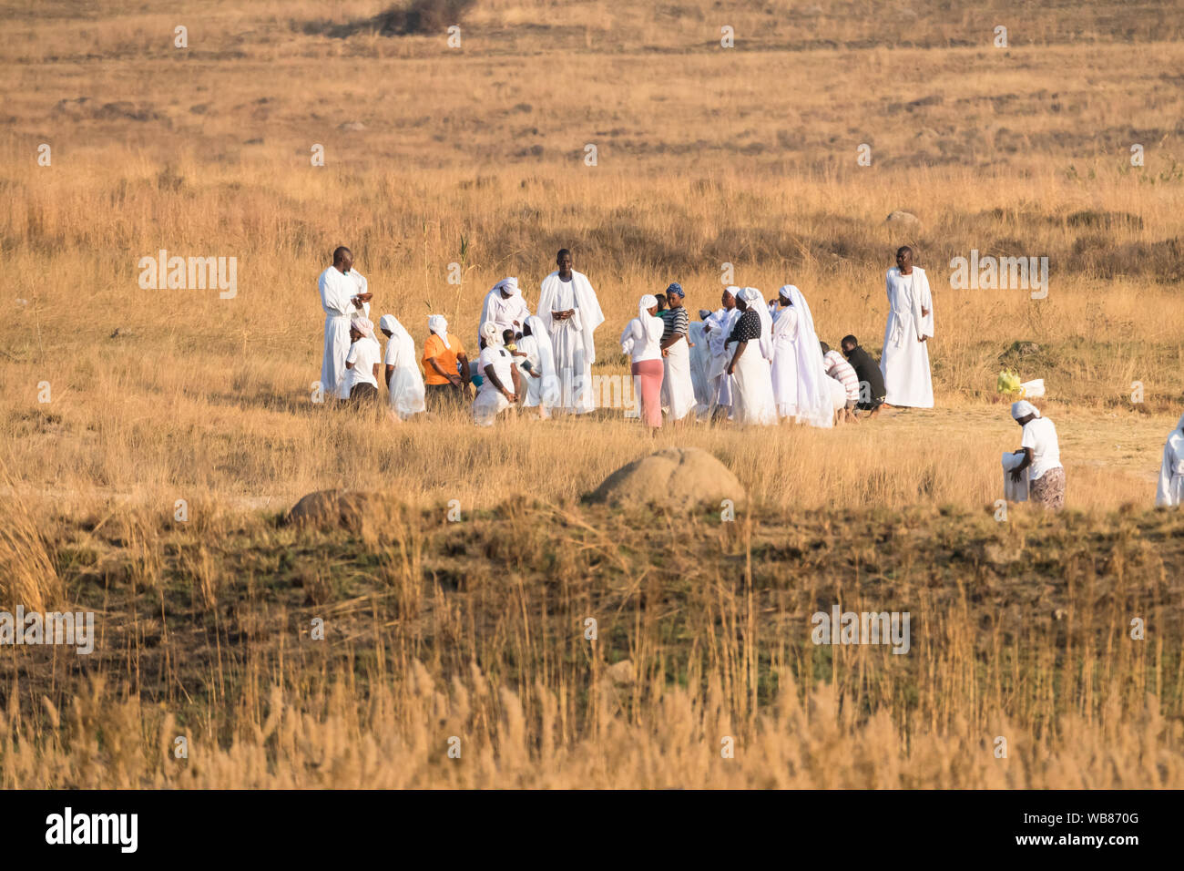 African black people dressed in white apparel or clothing holding a religious outdoor ceremony or meeting at sunset in Winter Johannesburg, Gauteng Stock Photo