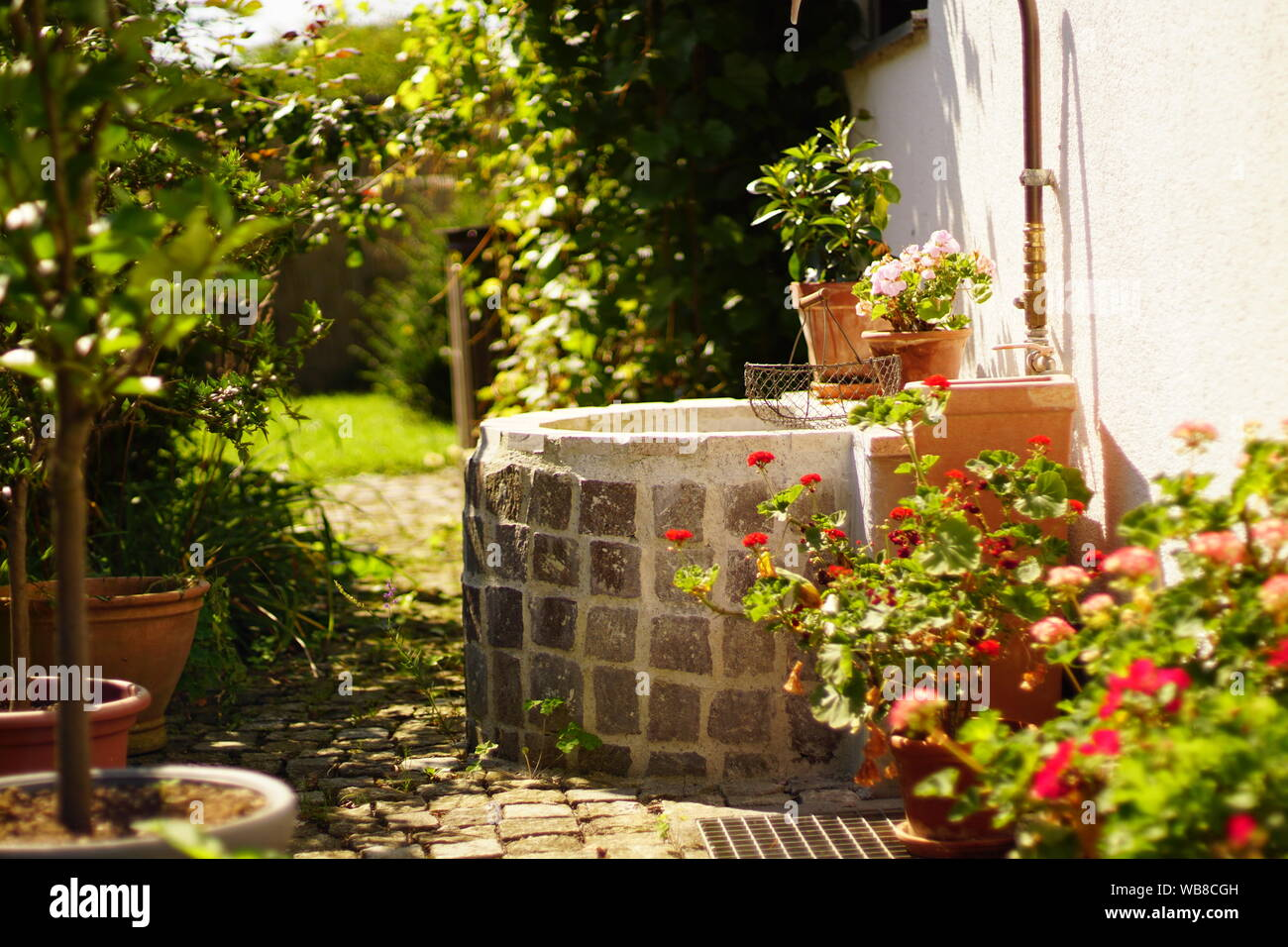 Beautiful garden with vintage water well in munich bavaria Stock Photo