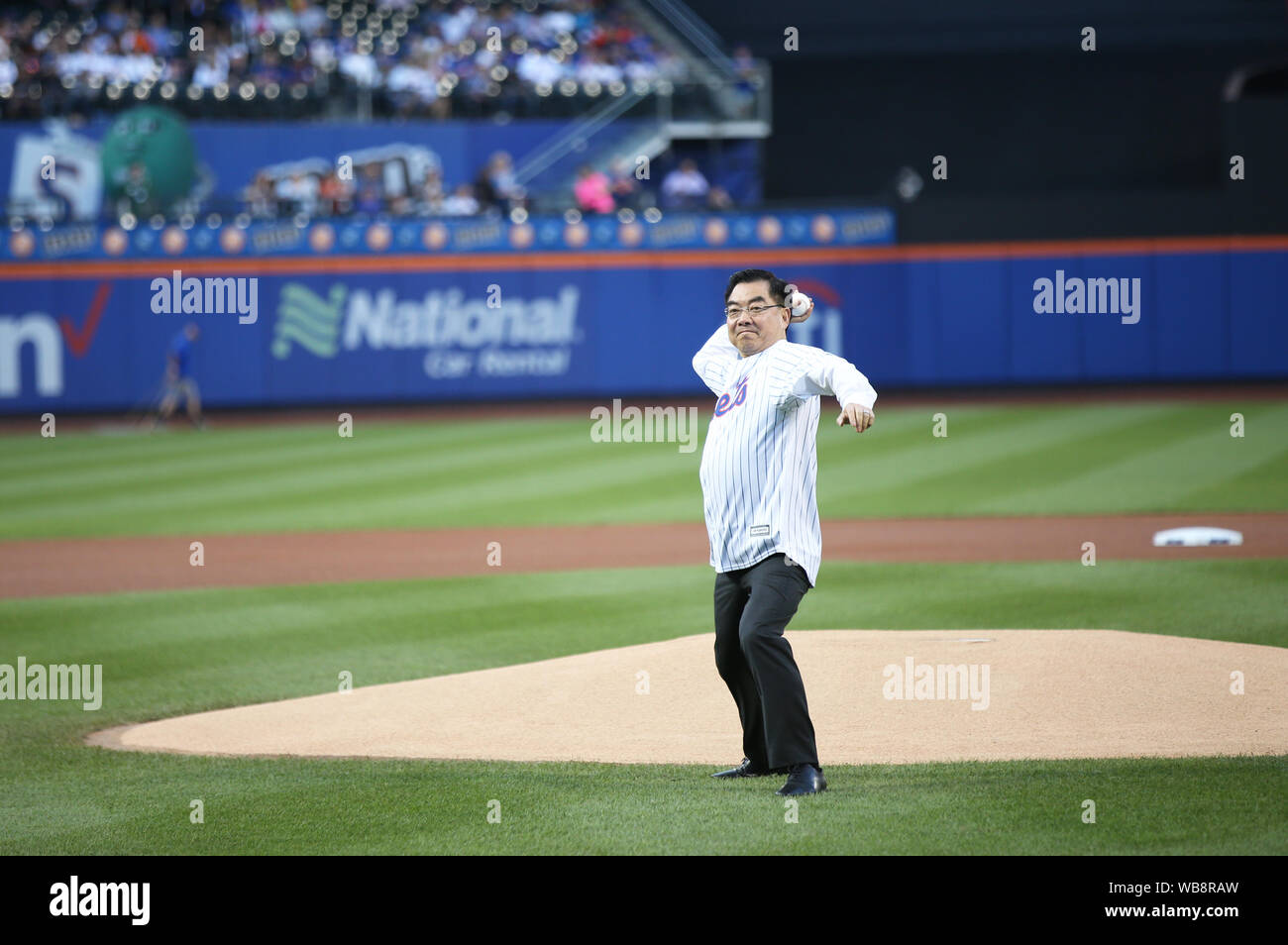 """New York, USA. 24th Aug, 2019. Huang Ping, Chinese Consul General in New York, throws a ceremonial first pitch to start an MLB game between the Mets and the Atlanta Braves in Citi Field, New York, the United States, Aug. 24, 2019. The 12th annual event """"An Evening of Chinese Culture"""" was held on Saturday evening in New York's Citi Field, an iconic stadium serving as the home field for the New York Mets. Credit: Qin Lang/Xinhua/Alamy Live News Stock Photo"""