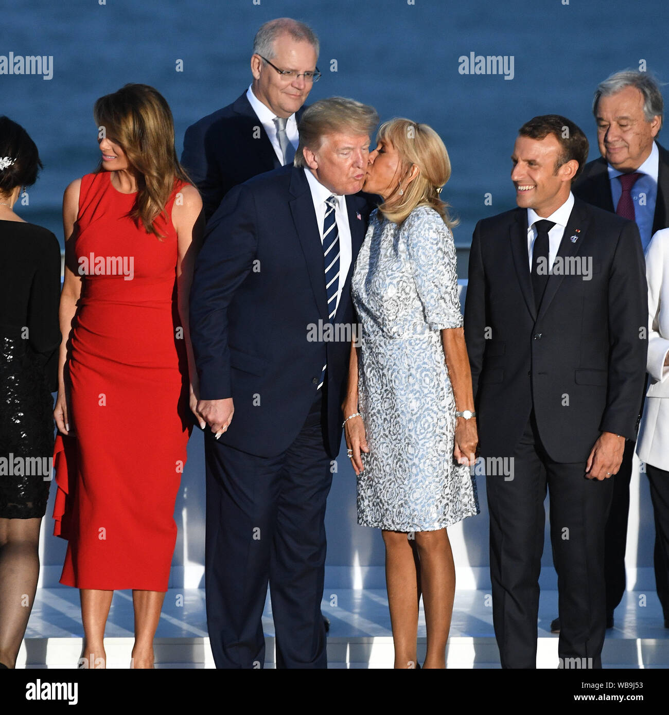 French President Emmanuel Macron Watches As His Wife Brigitte Macron Kisses President Donald Trump As He Stands With First Lady Melania Trump As They Join Other World Leaders For The Family Photo