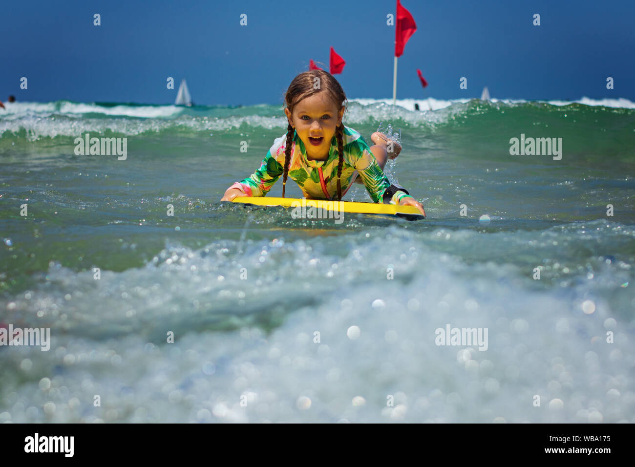Happy baby girl - young surfer ride on surfboard with fun on sea waves. Active family lifestyle Stock Photo