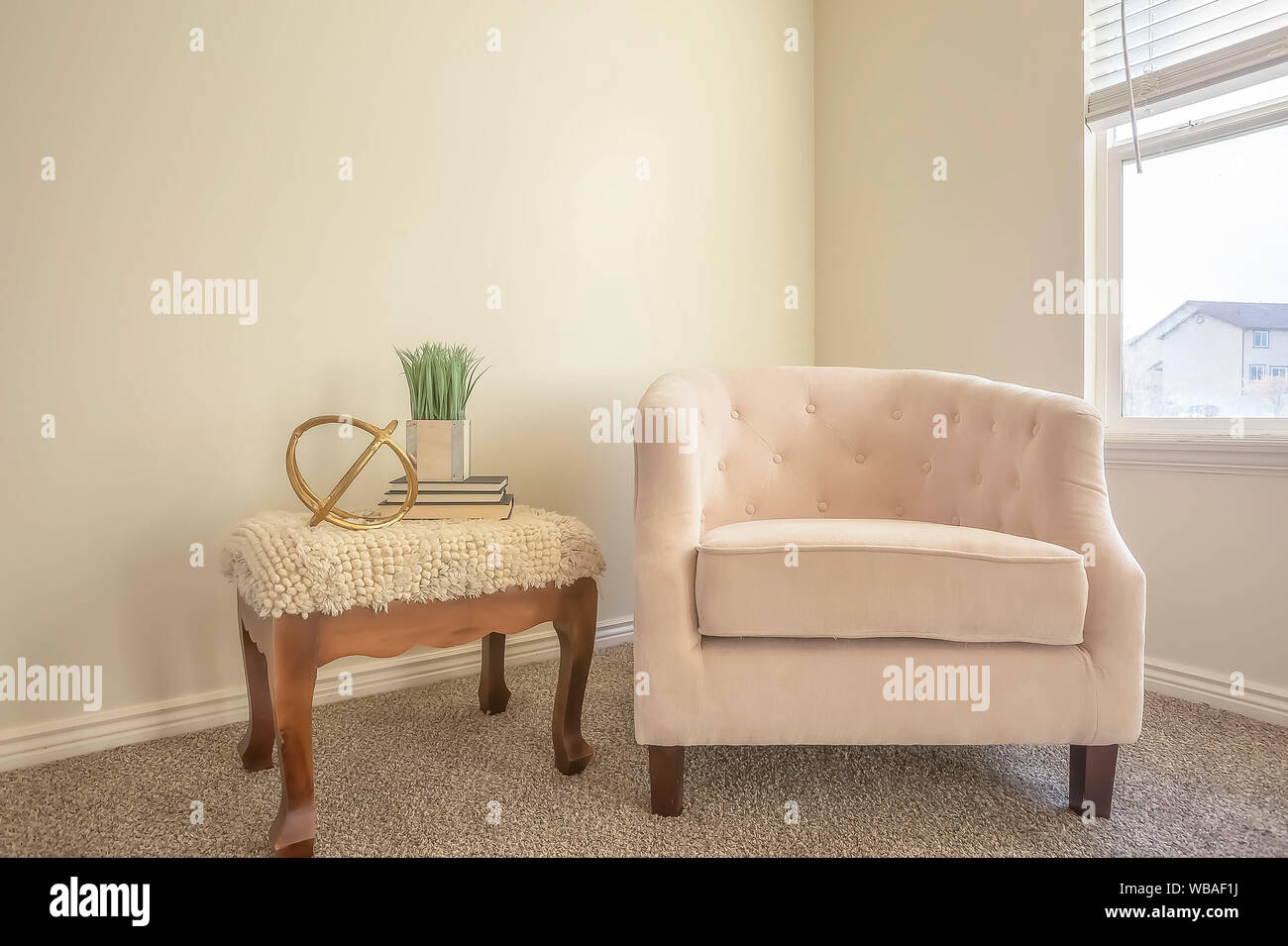 Cozy chair and wooden side table inside a room with white ...