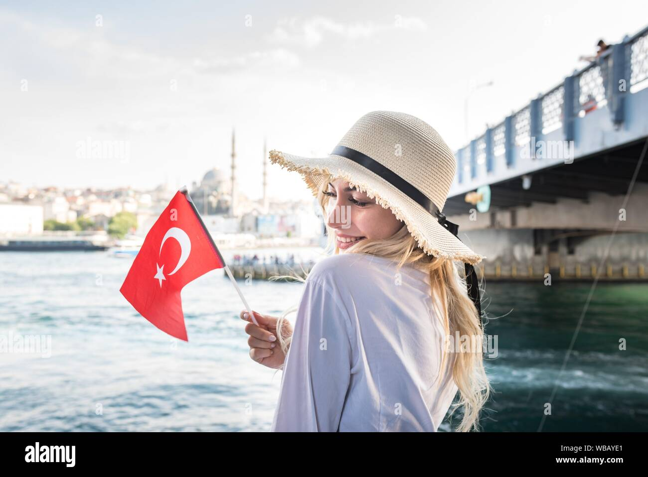 Attractive young beautiful girl waves Turkish flag over Galata Bridge and enjoys view of bosphorus in Istanbul,Turkey. Traveler concept. Stock Photo