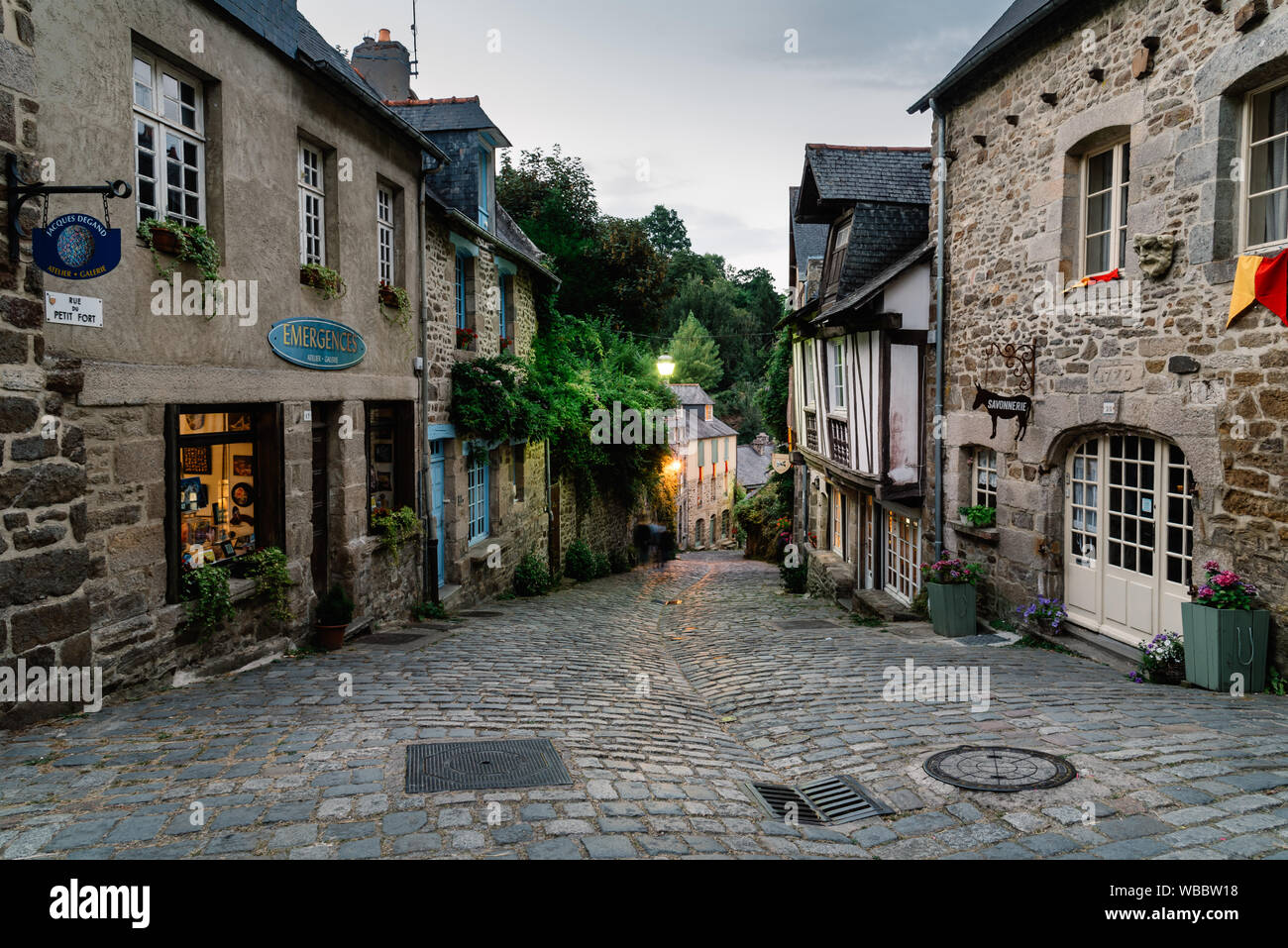 Dinan, France - July 23, 2018: Old cobblestoned street with medieval houses  at dusk, French Brittany Stock Photo