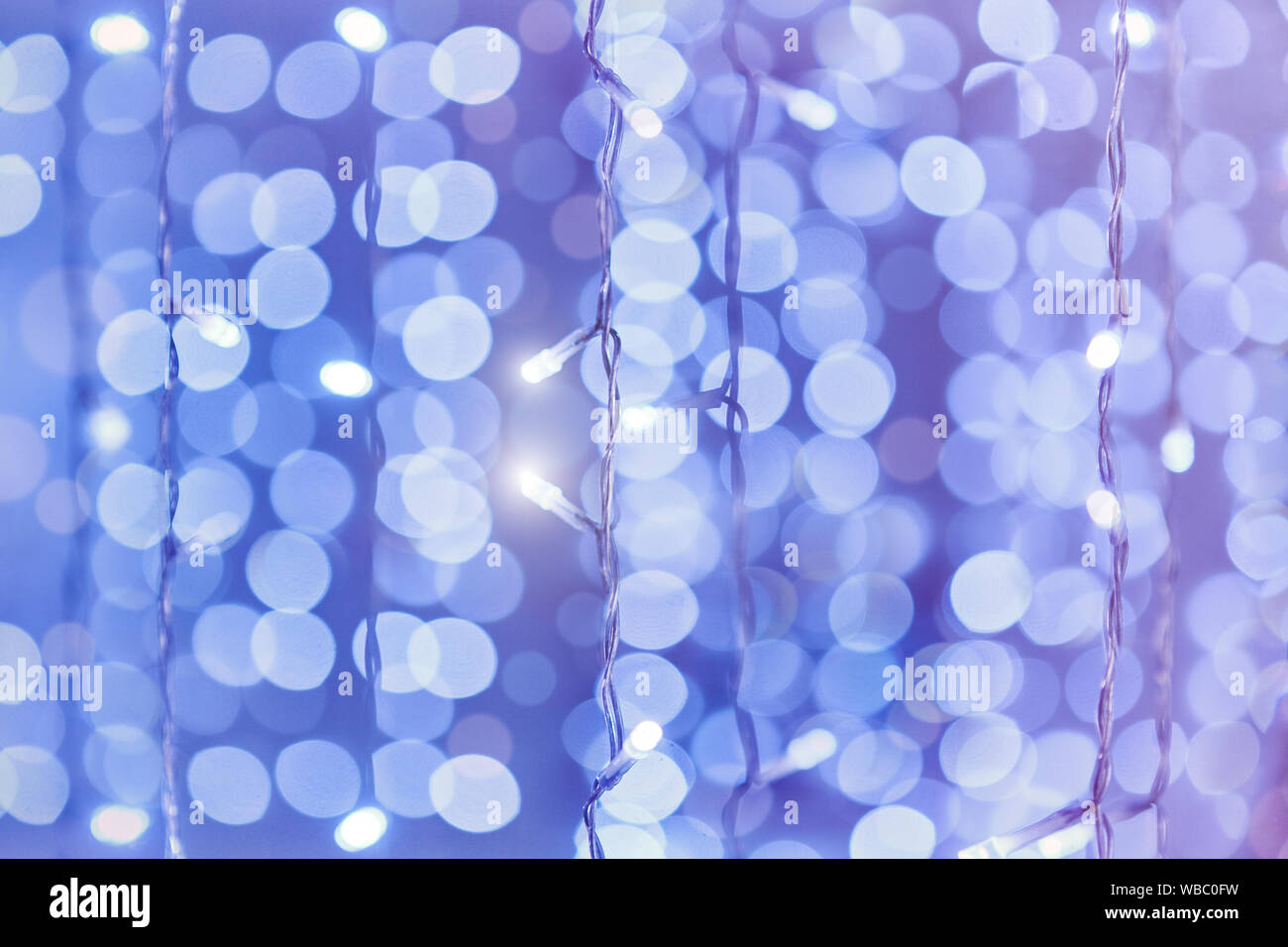 Soft colorful bokeh background. Luminous garlands of electric lights. Copy space to add text. Saturated colors. Blurry abstraction. Gentle tone. Stock Photo