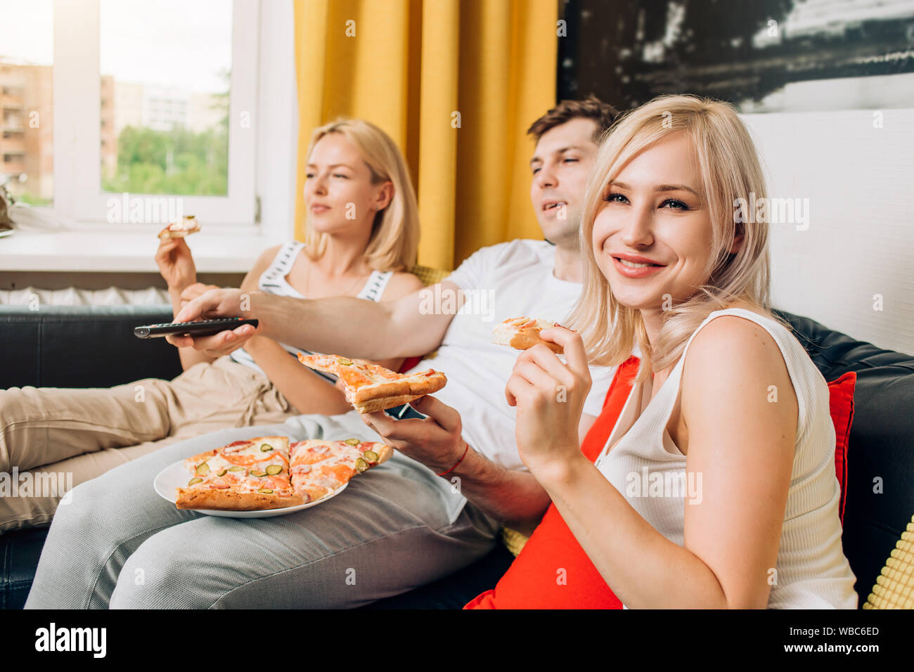Two blonde caucasian beautiful woman and man relaxing at home, watching tv, sitting on sofa and enjoying tasty pizza. Selective focus. Fast food, enjo Stock Photo