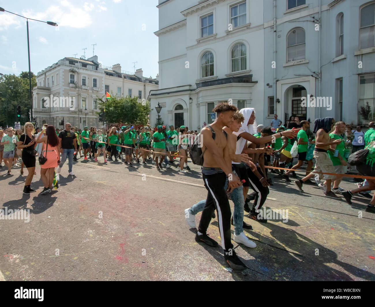 Masqueraders moving along a road behind a sound system truck. The main events of Notting Hill Carnival 2019 got underway on Sunday, with over a million revellers hitting the streets of West London, amongst floats, masqueraders, steel bands, and sound systems. Stock Photo