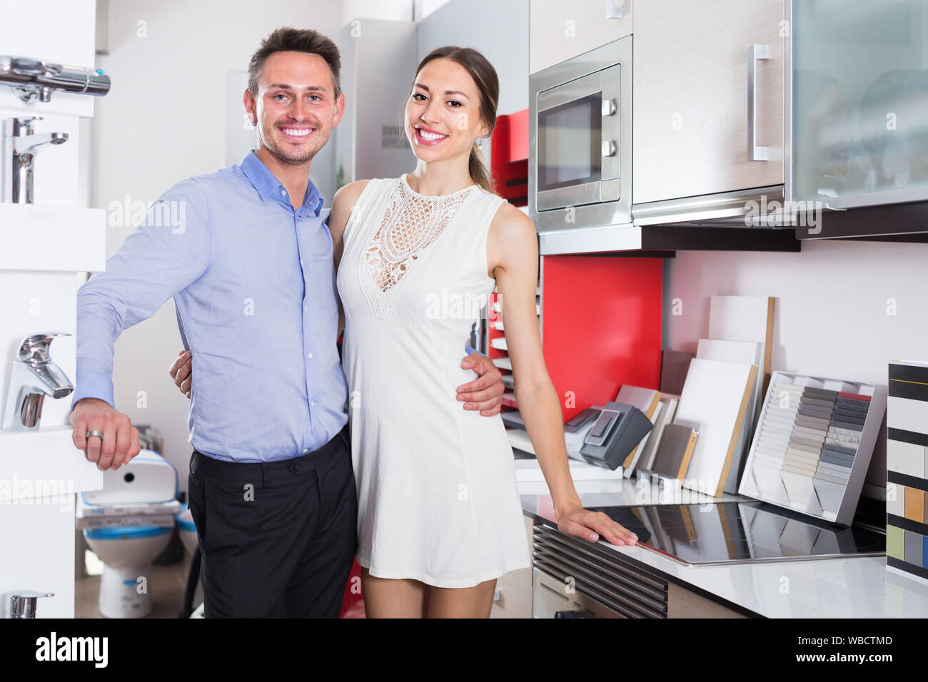 Young family couple looking at modern kitchen tabletop in