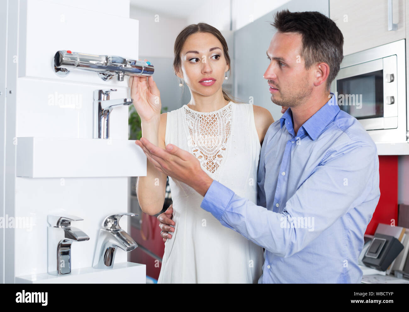 Married couple choosing faucet for kitchen in furniture workshop