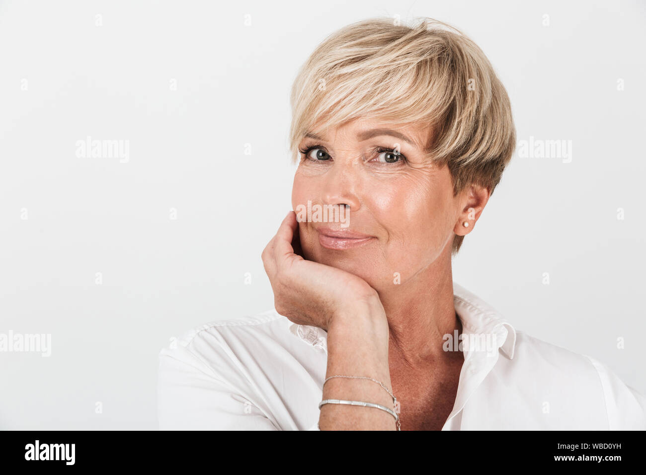 Portrait closeup of middle-aged woman with short blond hair looking at camera isolated over white background in studio Stock Photo