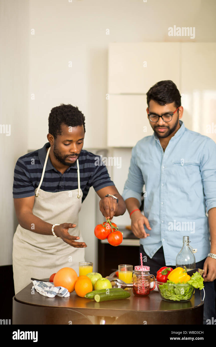 Shot of two male friends preparing vegetable salad in kitchen. Multi ethnic students cooking dinner together in hostel. Dieting, vegetarianism concept Stock Photo