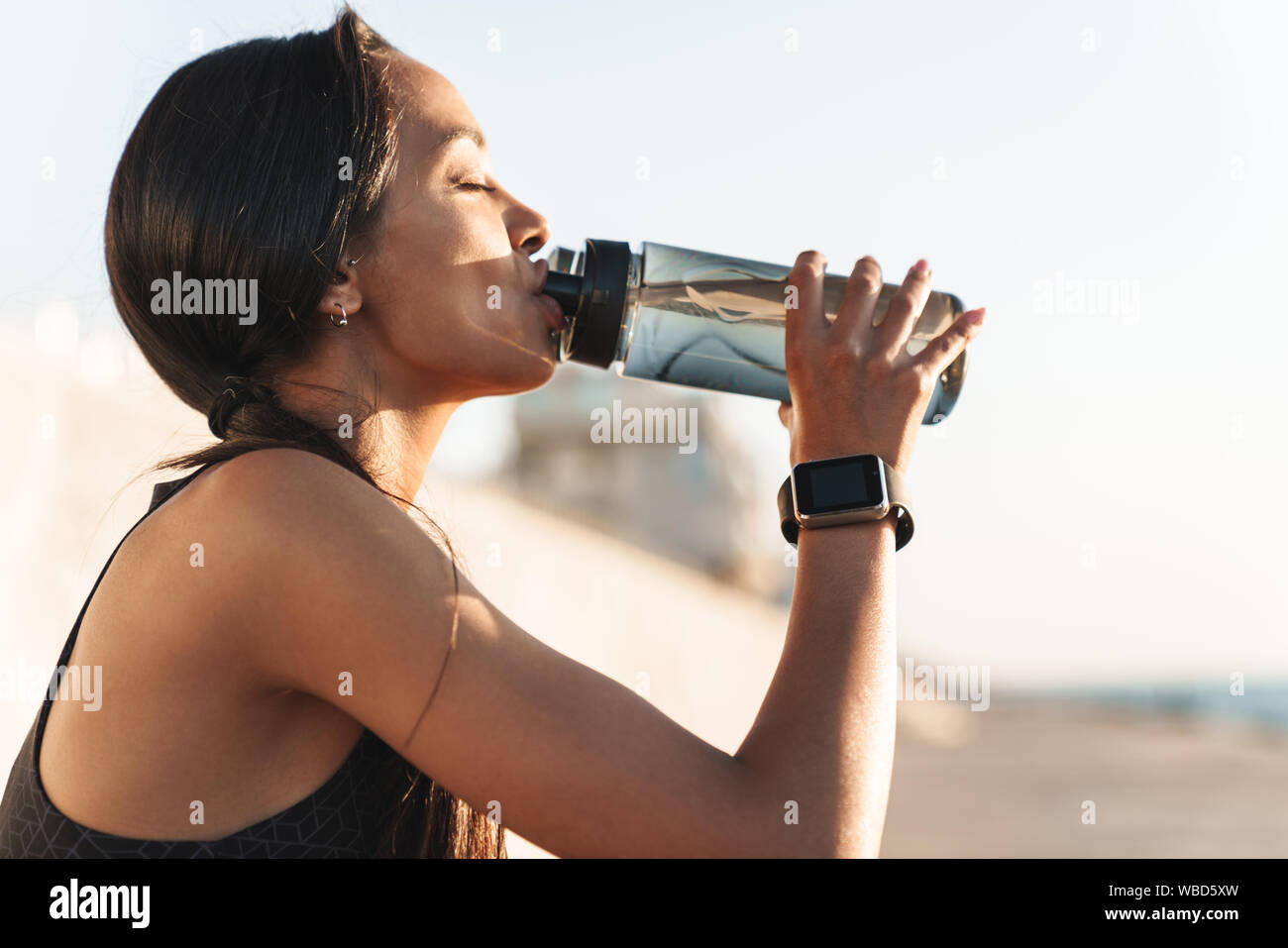 Close up of an attractive fit tired sportswoman outdoors, drinking water from a bottle Stock Photo