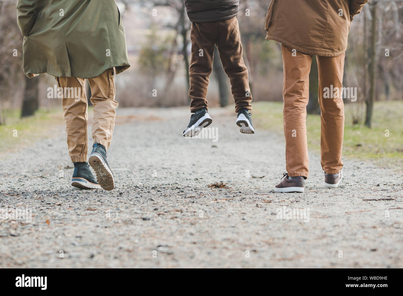 young beautiful family walking holding hands by city park Stock Photo