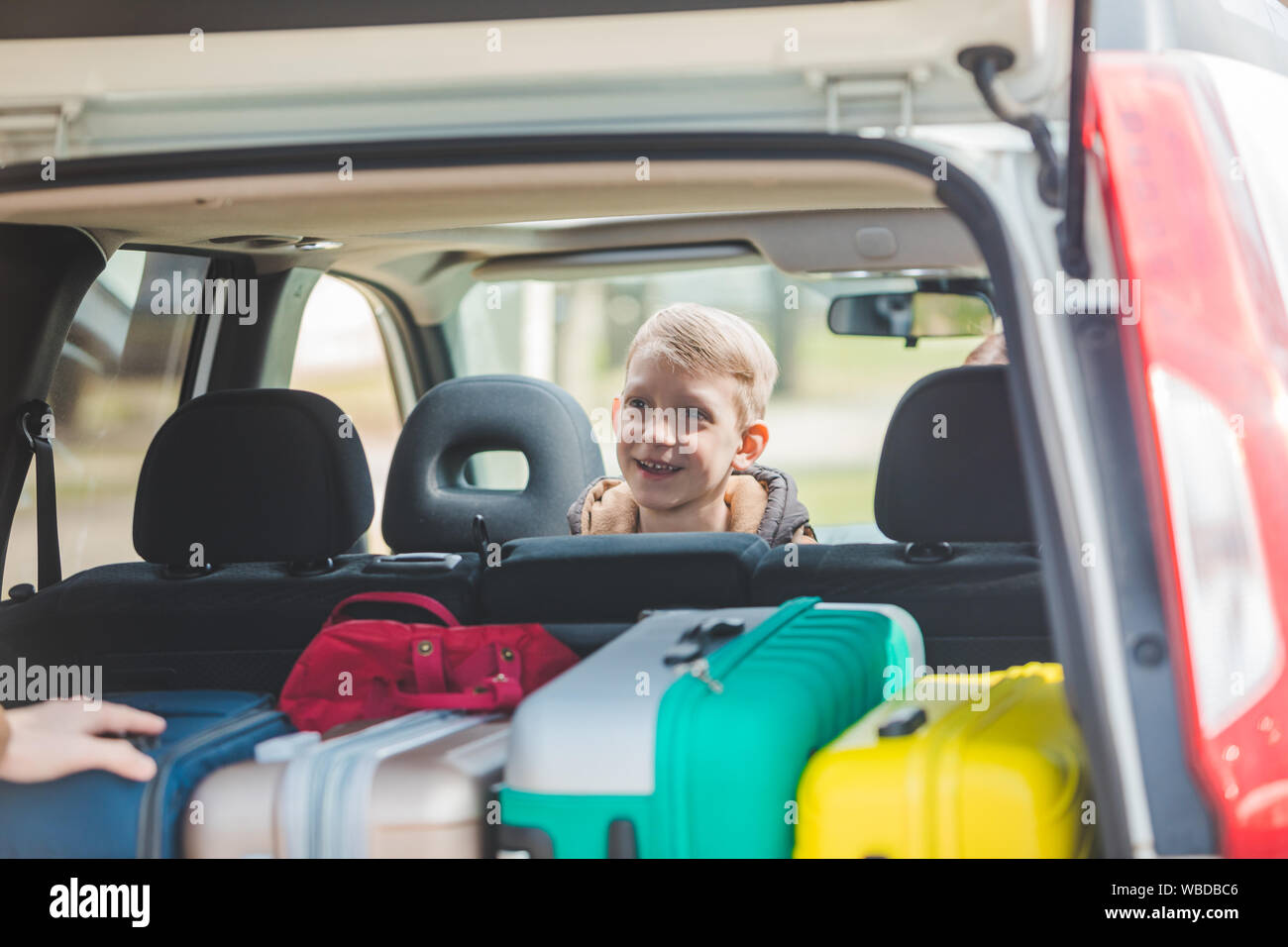 smiling little boy sitting in car waiting for car travel. bags in car trunk Stock Photo