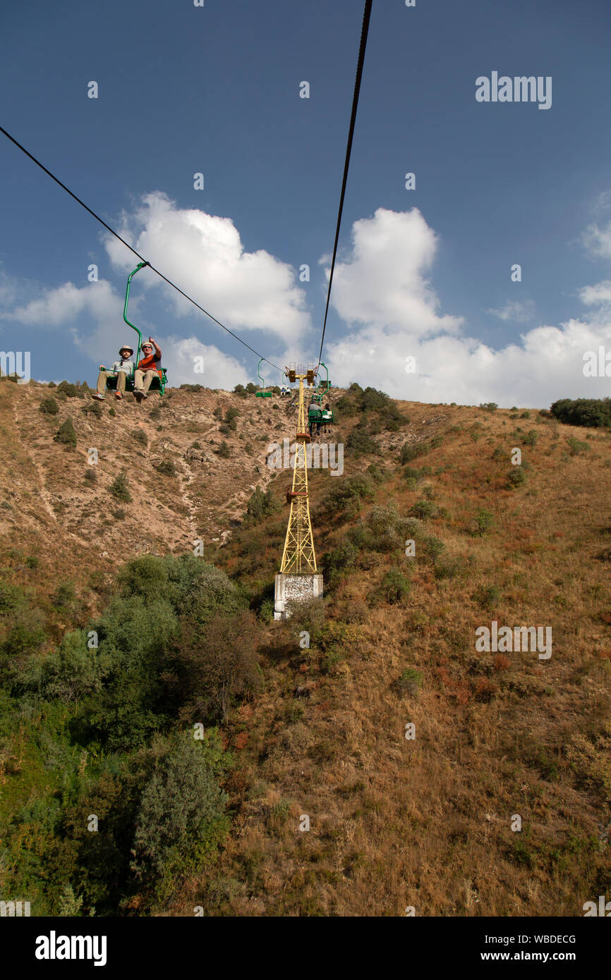 People on the chairlift in The Chatkal mountains in the Ugam-Chatkal National Park in Uzbekistan. Used for skiers in the winter, and hikers in the sum. Stock Photo