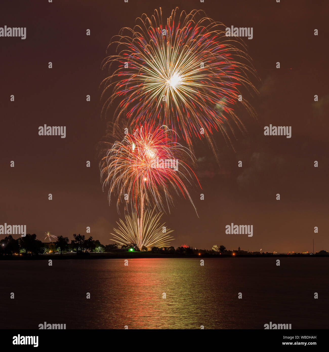 Fireworks Over A Lake - Colorful Fourth of July fireworks light up night sky over Marston Lake, Denver, Colorado, USA. Stock Photo